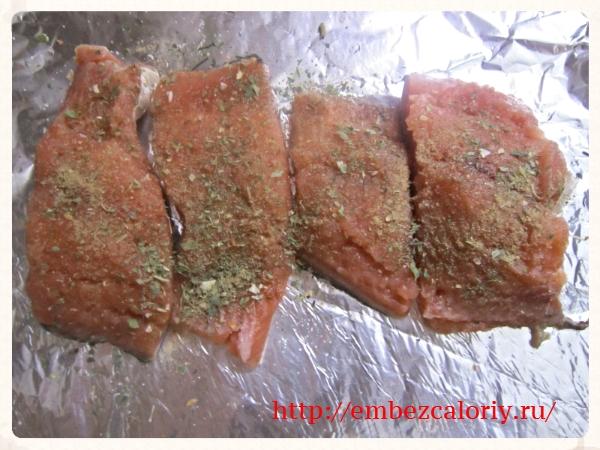 Укладываем рыбу на фольгу, посыпаем пряностями и солью