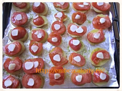 На кружочки помидор укладываем чеснок