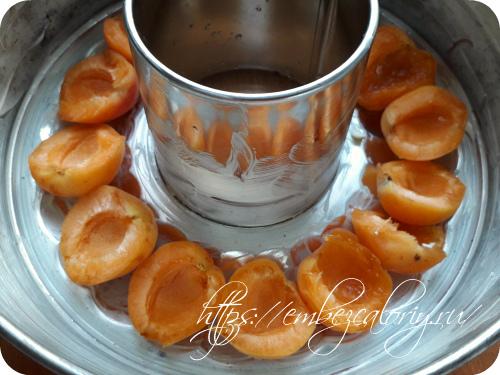 Разъемную форму смазываем маслом и укладываем половинки абрикосов